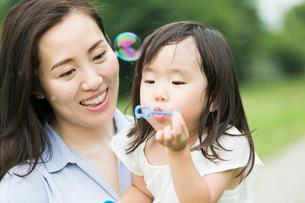 シャボン玉で遊ぶ親子の写真素材 [FYI01815000]