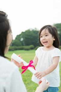 母親にプレゼントを渡す女の子の写真素材 [FYI01815039]