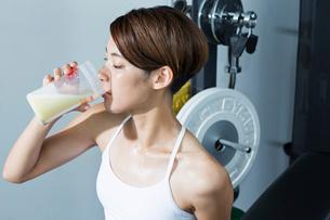 ジムでプロテインを飲む若い女性の写真素材 [FYI01815097]