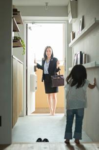 帰宅したビジネスウーマンを出迎える女の子の写真素材 [FYI01815110]