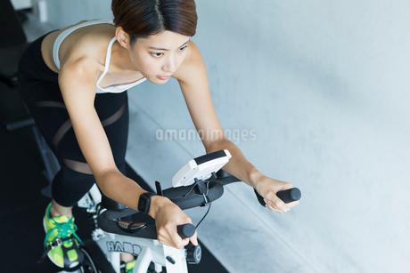 ジムでエアロバイクを漕ぐ若い女性の写真素材 [FYI01815115]