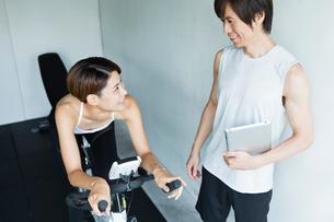 エアロバイクを漕ぐ若い女性と会話するトレーナーの写真素材 [FYI01815131]