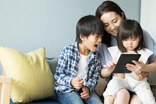 タブレットを操作する女性と子供たちの写真素材 [FYI01815134]