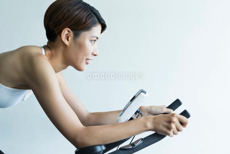 ジムでエアロバイクを漕ぐ若い女性の写真素材 [FYI01815137]