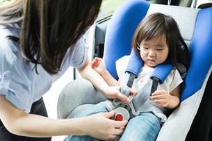 子供をチャイルドシートに乗せる母親の写真素材 [FYI01815144]