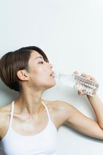 水を飲むスポーツウェアの若い女性の写真素材 [FYI01815145]