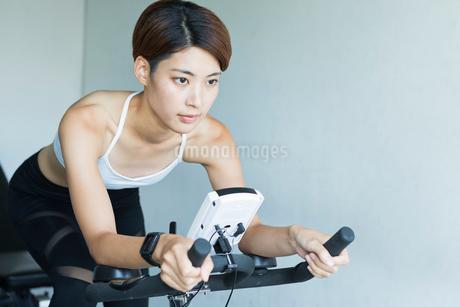 ジムでエアロバイクを漕ぐ若い女性の写真素材 [FYI01815147]