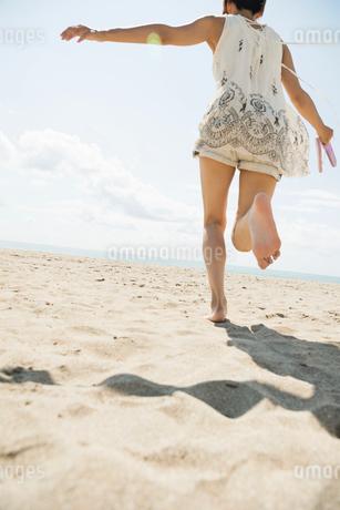 砂浜を思い切り走る20代女性の写真素材 [FYI01815169]