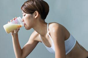 ジムでプロテインを飲む若い女性の写真素材 [FYI01815174]