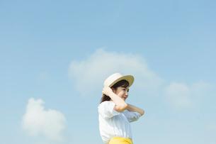 麦わら帽子を抑える女性の写真素材 [FYI01815208]