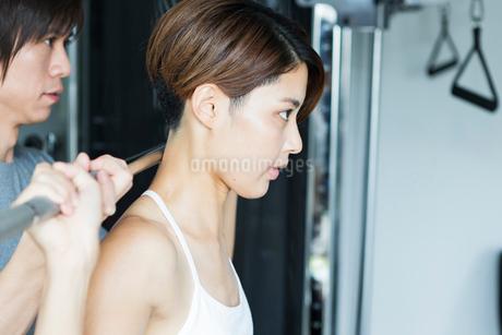 ダンベルをあげる若い女性とトレーナーの写真素材 [FYI01815209]