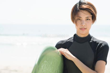 サーフボードを持つウェットスーツを着た20代女性の写真素材 [FYI01815214]