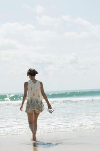 砂浜を歩く20代女性の後ろ姿の写真素材 [FYI01815234]
