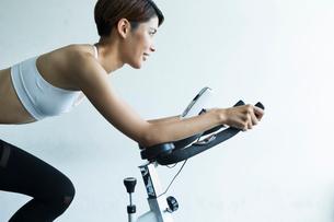ジムでエアロバイクを漕ぐ若い女性の写真素材 [FYI01815251]