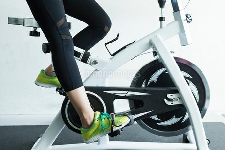 ジムでエアロバイクを漕ぐ若い女性の足元の写真素材 [FYI01815253]