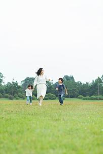 笑顔で手をつないで走る親子の写真素材 [FYI01815267]