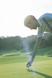 ゴルフボールを拾う20代女性の写真素材 [FYI01815268]