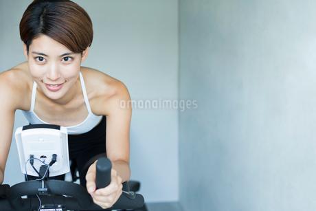 ジムでエアロバイクを漕ぐ若い女性の写真素材 [FYI01815283]