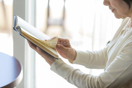 本のページをめくるシニア女性の手元の写真素材 [FYI01815284]