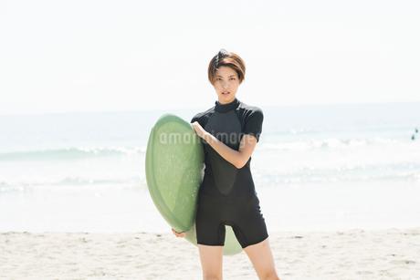 サーフボードを持つウェットスーツを着た20代女性の写真素材 [FYI01815294]