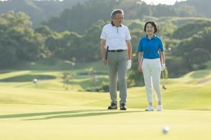 ゴルフコースを歩くシニア夫婦の写真素材 [FYI01815297]