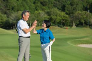 ゴルフ場でハイタッチをするシニア夫婦の写真素材 [FYI01815329]