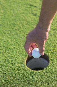 ホールからゴルフボールを取り出すシニア男性の手元の写真素材 [FYI01815370]