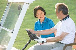 ゴルフカーに乗るシニア夫婦の写真素材 [FYI01815422]