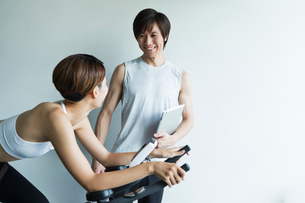 エアロバイクを漕ぐ若い女性と会話するトレーナーの写真素材 [FYI01815429]