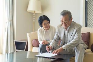 契約書にサインするシニア夫婦の写真素材 [FYI01815441]