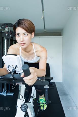 ジムでエアロバイクを漕ぐ若い女性の写真素材 [FYI01815445]