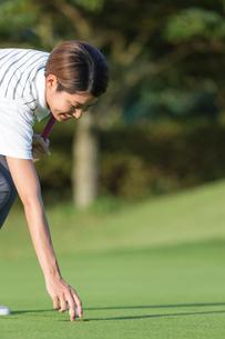 ゴルフボールを拾う20代女性の写真素材 [FYI01815482]