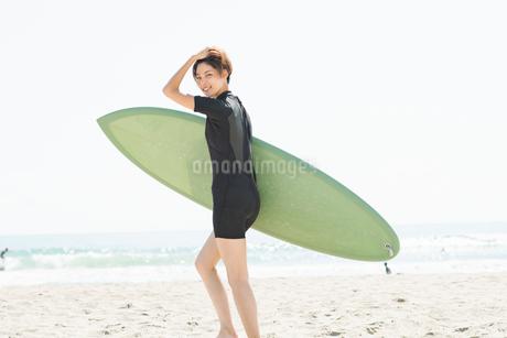 サーフボードを持つウェットスーツを着た20代女性の写真素材 [FYI01815522]