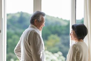 窓辺で会話するシニア夫婦の写真素材 [FYI01815539]