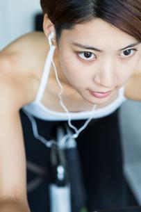 ジムでエアロバイクを漕ぐ若い女性の写真素材 [FYI01815540]