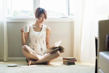 コーヒーを飲みながら読書をする20代女性の写真素材 [FYI01815553]