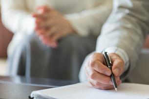 契約書にサインするシニア夫婦の手元の写真素材 [FYI01815609]