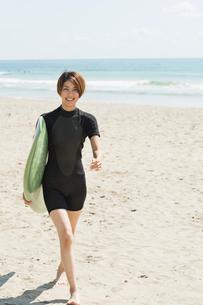 サーフボードを持つウェットスーツを着た20代女性の写真素材 [FYI01815612]