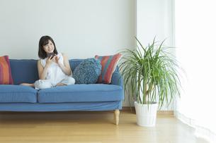 ソファーに座りスマートフォンを操作する女性の写真素材 [FYI01815679]