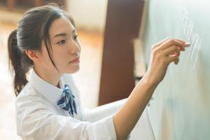 黒板に記入する女子高校生の写真素材 [FYI01815740]