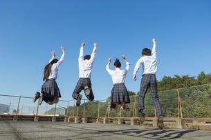 屋上でジャンプする高校生の写真素材 [FYI01815833]