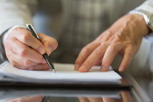 契約書にサインするシニア男性の手元の写真素材 [FYI01815868]