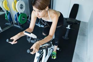 ジムでエアロバイクを漕ぐ若い女性の写真素材 [FYI01815873]
