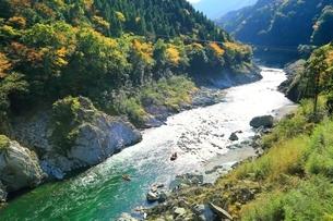 紅葉の小歩危峡とラフティングの写真素材 [FYI01819610]