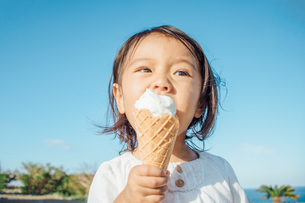 ソフトクリームを頬張る子供の写真素材 [FYI01819942]