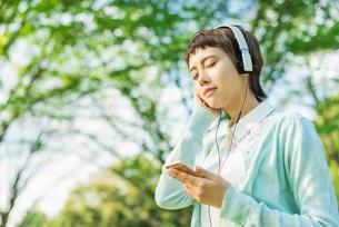 公園で音楽を聴く女性の写真素材 [FYI01820236]