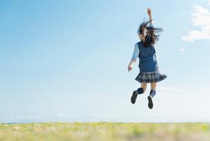 女子高生 海 草原 ジャンプの写真素材 [FYI01820352]
