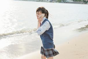 女子高生 海 裸足 スマホ通話の写真素材 [FYI01820357]