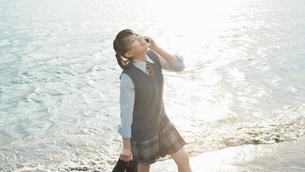 女子高生 海 裸足 スマホ通話の写真素材 [FYI01820361]