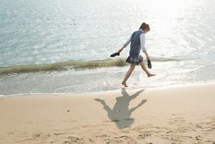 女子高生 海 裸足 歩く 影の写真素材 [FYI01820362]